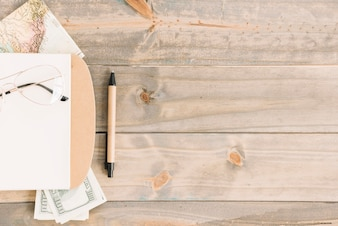 Óculos; bloco de anotações; moeda; mapa e caneta no fundo da prancha de madeira