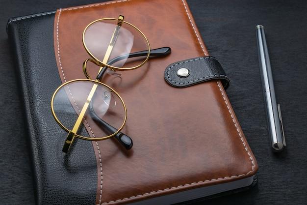 Óculos, bloco de notas e caneta sobre uma mesa escura.