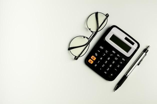 Óculos, calculadora ee uma caneta na mesa branca. - vista de cima com espaço de cópia.