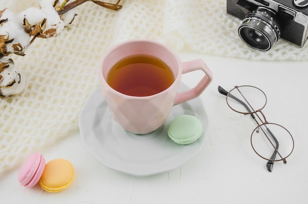 Óculos; câmera; galho de algodão com xícara de chá de ervas e macaroons em pano de fundo branco