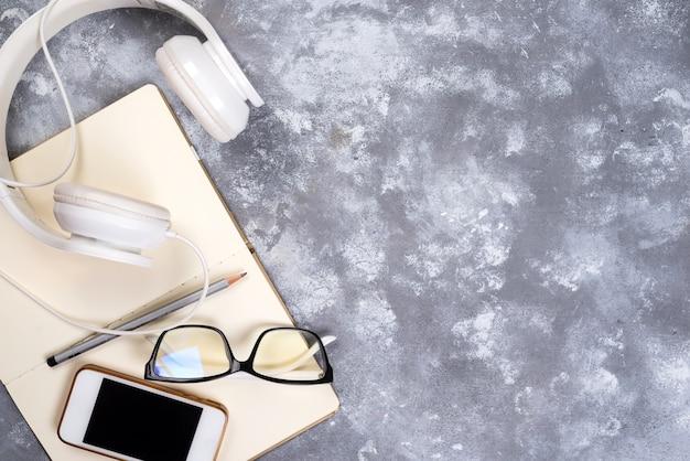 Óculos, caneta, caderno e telefone com fones de ouvido no fundo de pedra.