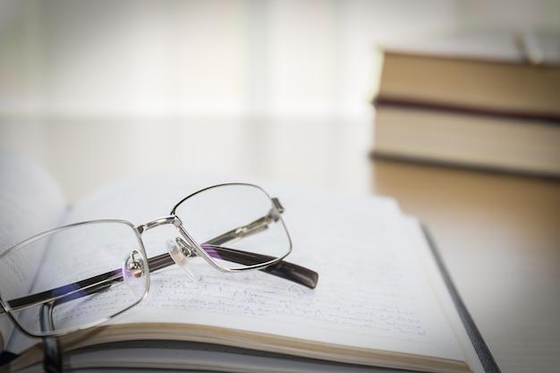 Óculos, colocar no caderno na mesa de madeira