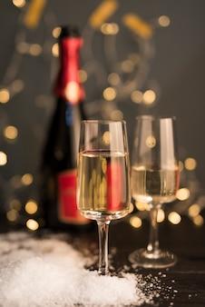 Óculos com bebida a bordo perto de neve e garrafa de ornamento