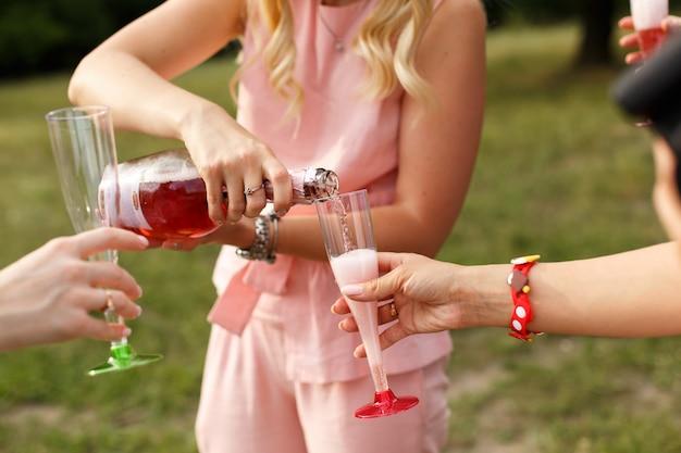 Óculos com champanhe nas mãos. o piquenique da mulher no parque de domingo.