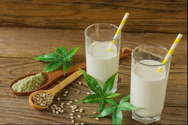 Óculos com folhas de cannabis e glúten vegan à base de ervas cannabis e leite sem lactose na mesa de madeira.