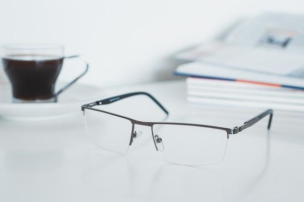 Óculos com livro e café