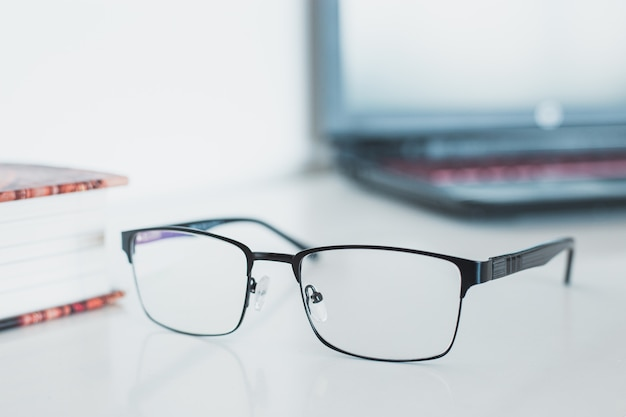 Óculos com livro e computador portátil