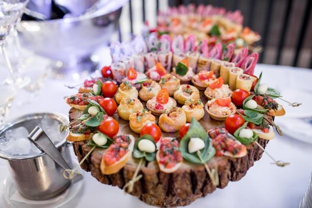 Óculos com martini e pratos de madeira com aperitivos em uma mesa de jantar
