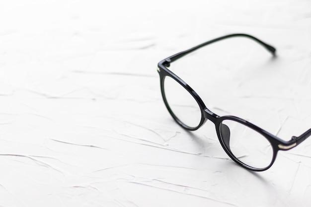 Óculos com moldura preta em fundo branco. óculos. óculos redondos com lentes transparentes. feche os óculos com técnica embaçada. acessório de moda. tema da oftalmologia.