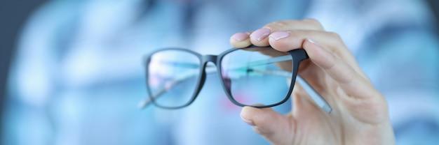 Óculos com ótica preta são mantidos em mãos, seleção de óculos para o conceito de visão