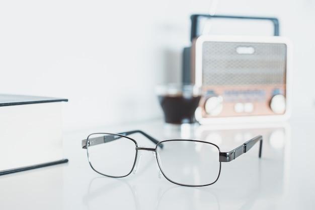 Óculos com rádio, livro e café