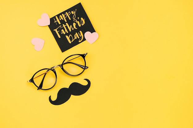 Óculos com um bigode de papel preto e um cartão de felicitações