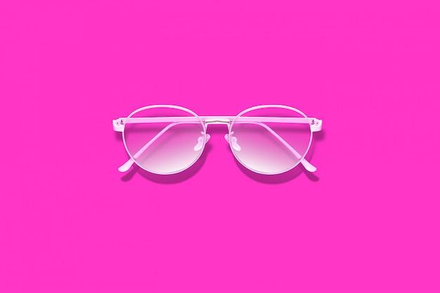 Óculos cor de rosa elegantes na superfície rosa