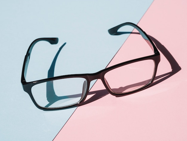 Óculos de armação preta sobre fundo azul e rosa