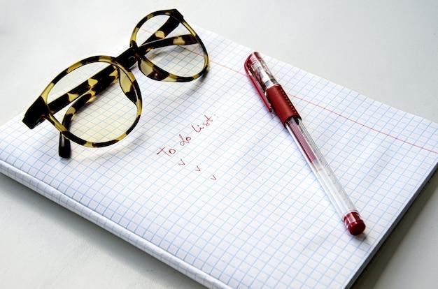 Óculos de aro de chifre, caneta de tinta vermelha em um caderno quadriculado. a folha diz