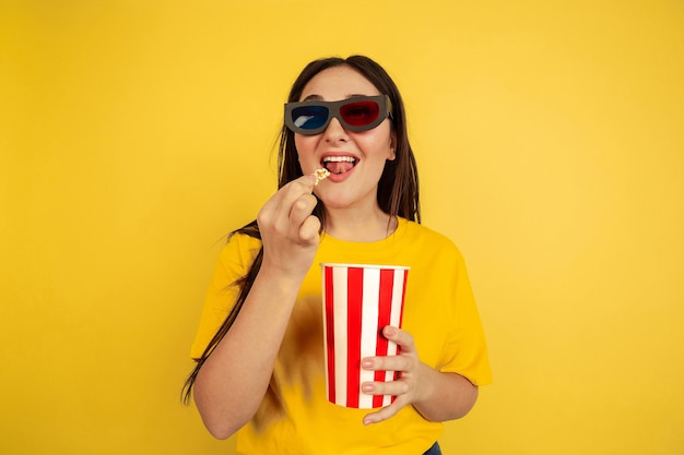 Óculos de cinema 3d e pipoca. retrato da mulher caucasiana isolado na parede amarela. bela modelo em estilo casual. conceito de emoções humanas, expressão facial, vendas, copyspace.