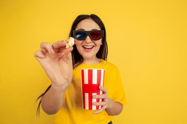 Óculos de cinema 3d e pipoca. retrato da mulher caucasiana isolado no fundo amarelo do estúdio. bela modelo em estilo casual. conceito de emoções humanas, expressão facial, vendas, anúncio, copyspace.