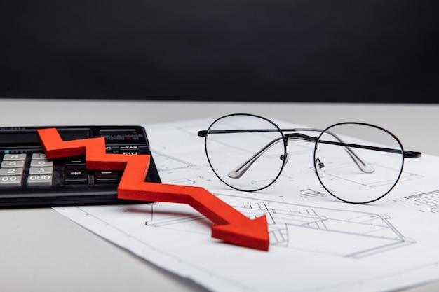 Óculos de conceito financeiro e de investimento calc e seta para baixo no close up do projeto arquitetônico