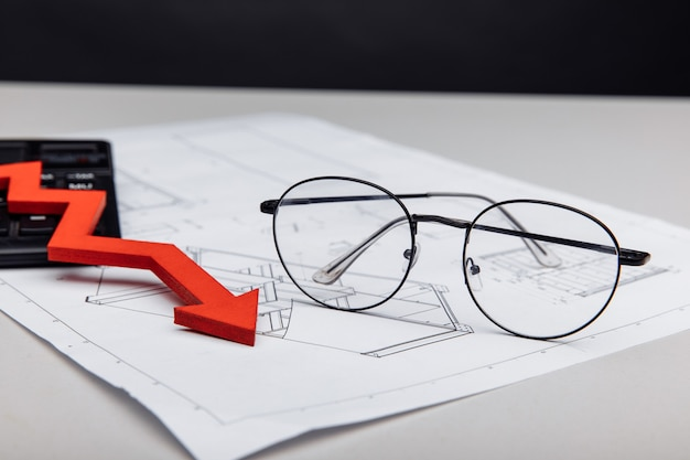 Óculos de conceito financeiro e de investimento e seta para baixo no close up do projeto arquitetônico
