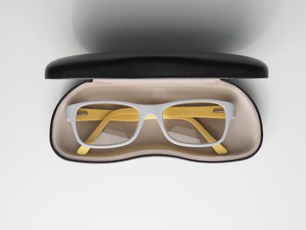 Óculos de cor cinza e amarelo com caixa para óculos em branco.