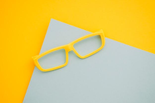 Óculos de crianças amarelas sobre fundo cinza e amarelo