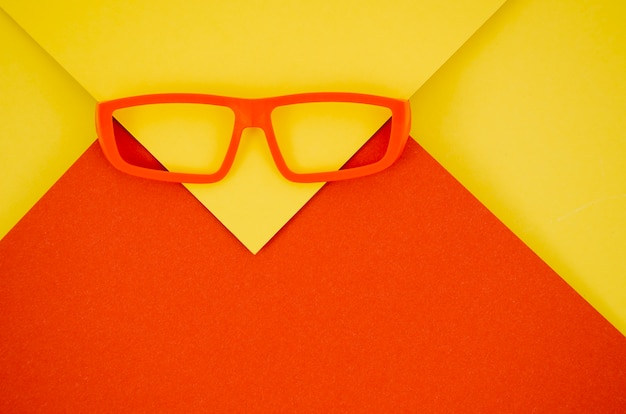 Óculos de crianças vermelhas sobre fundo vermelho e amarelo