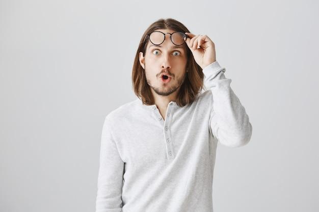 Óculos de decolagem de cara bonito impressionado e parecendo surpreso