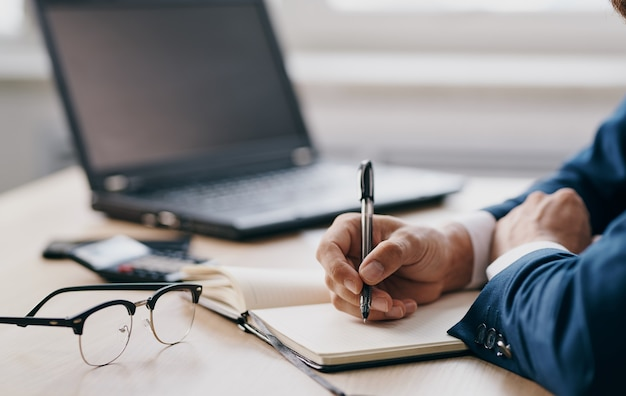 Óculos de documentos de finanças de negócios de mãos masculinas abrem o escritório do laptop e o bloco de notas. foto de alta qualidade