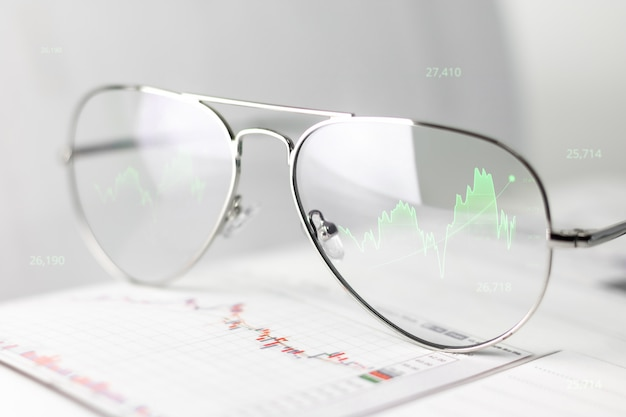 Óculos de homem de negócios, mostrando os lucros e gráfico de ações na tela de lente óptica. os óculos de realidade virtual mostram o efeito de uma economia crescente em termos de dinheiro e economia.