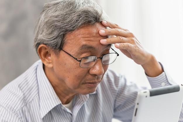 Óculos de homem velho asiático sênior dor de cabeça de usar e procurando a tela do tablet