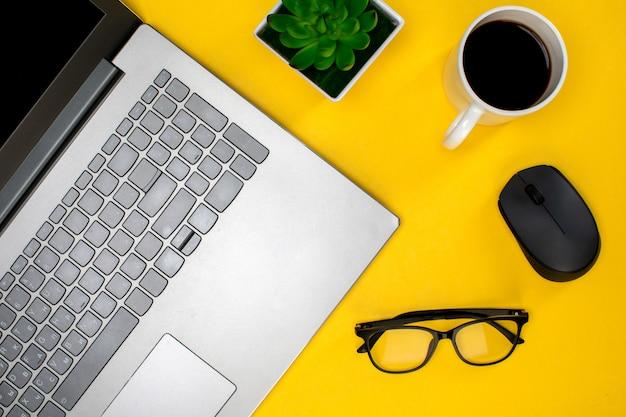 Óculos de laptop e mouse com xícara de café