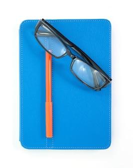 Óculos de leitura com livro azul e caneta isolado no branco
