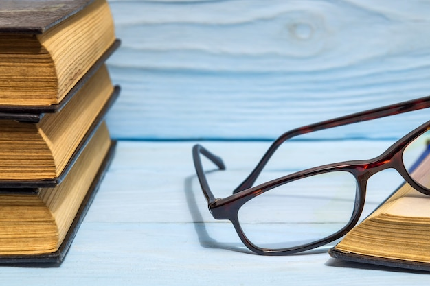 Óculos de leitura e uma pilha de livros