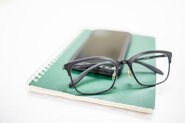 Óculos de leitura no smartphone móvel e caderno verde na mesa branca.
