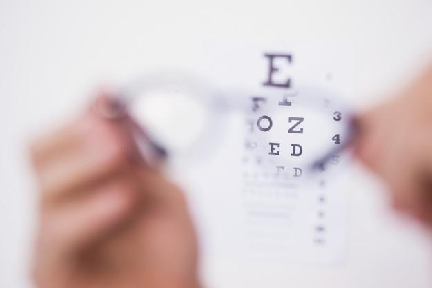 Óculos de leitura olhando exame de olho