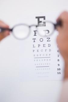 Óculos de leitura, olhando para o teste do olho