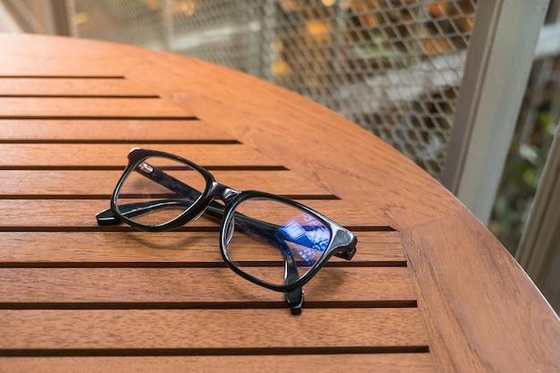 Óculos de leitura preta na mesa de madeira