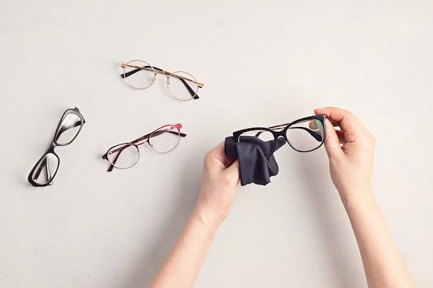 Óculos de limpeza de mão de mulher. loja de ótica, seleção de óculos, exame de vista, exame de visão no oculista, conceito de acessórios de moda. vista superior, configuração plana
