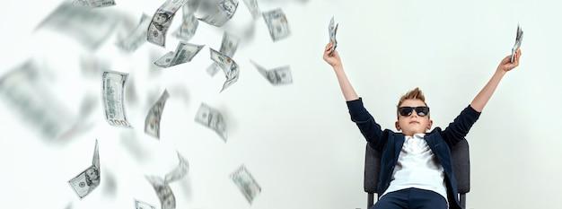 Óculos de menino detém dólares e sabe como ganhar dinheiro no contexto de notas caindo