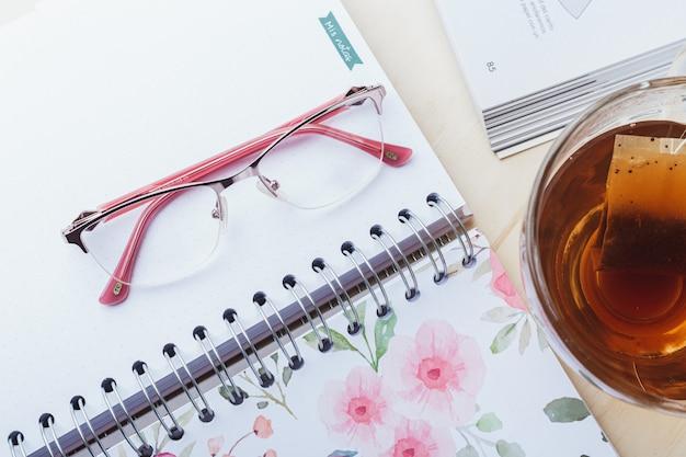 Óculos de mulher com chá e livros