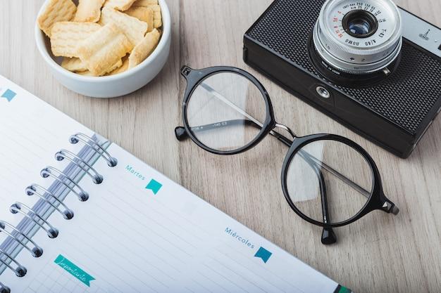 Óculos de mulher com planejador, biscoitos e câmera