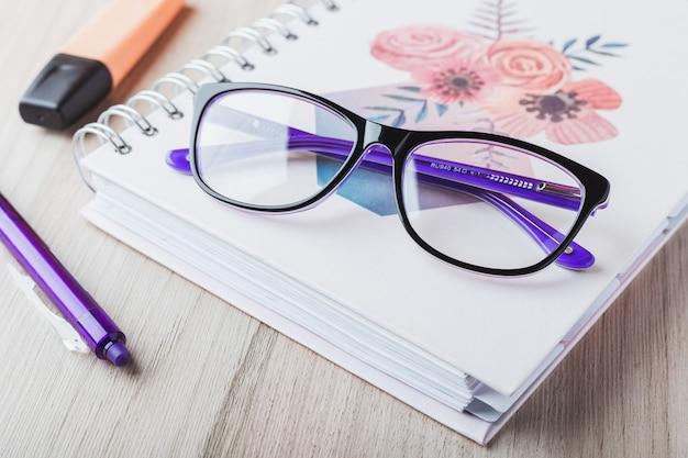 Óculos de mulher com planejador e lápis