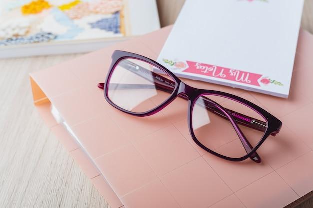 Óculos de mulher com planejador e livros