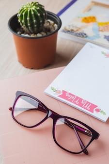 Óculos de mulher com planejador e planta