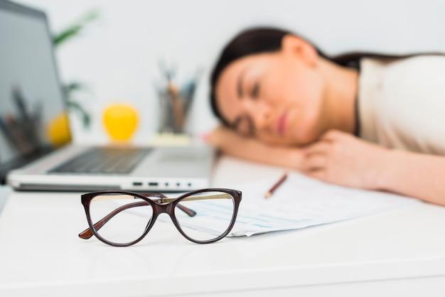 Óculos de mulher dormindo na mesa no escritório