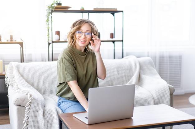 Óculos de mulher usando um laptop enquanto está sentado no sofá com uma grande janela no interior da casa