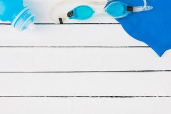 Óculos de natação azuis; garrafa de água e guardanapo na mesa de madeira branca