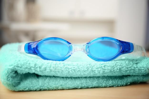 Óculos de natação com toalha na mesa de madeira