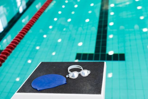 Óculos de natação e boné na piscina