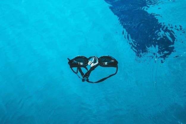 Óculos de natação estão no parapeito perto da piscina